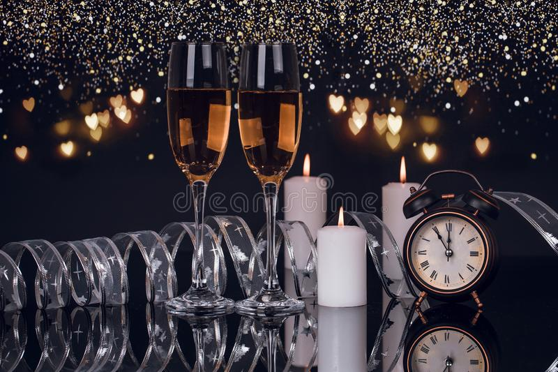 Δύο γυαλιά με τη σαμπάνια, το ρολόι, τα φω'τα και τα κεριά στοκ εικόνα