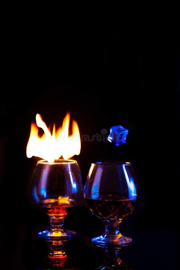Δύο γυαλιά με το κάψιμο του οινοπνεύματος και του πάγου στο σκοτεινό υπόβαθρο στοκ εικόνα με δικαίωμα ελεύθερης χρήσης