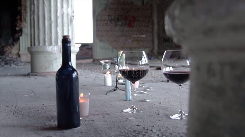 Δύο γυαλιά με το μπουκάλι κρασιού κεριών στο γκρίζο υπόβαθρο footage Ρομαντική ακόμα ζωή με το κρασί και τα κεριά για δύο μέσα στοκ φωτογραφία