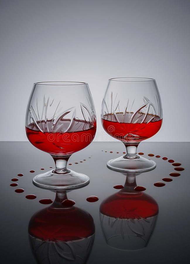 Δύο γυαλιά της στάσης κόκκινου κρασιού στην επιφάνεια καθρεφτών στοκ εικόνα