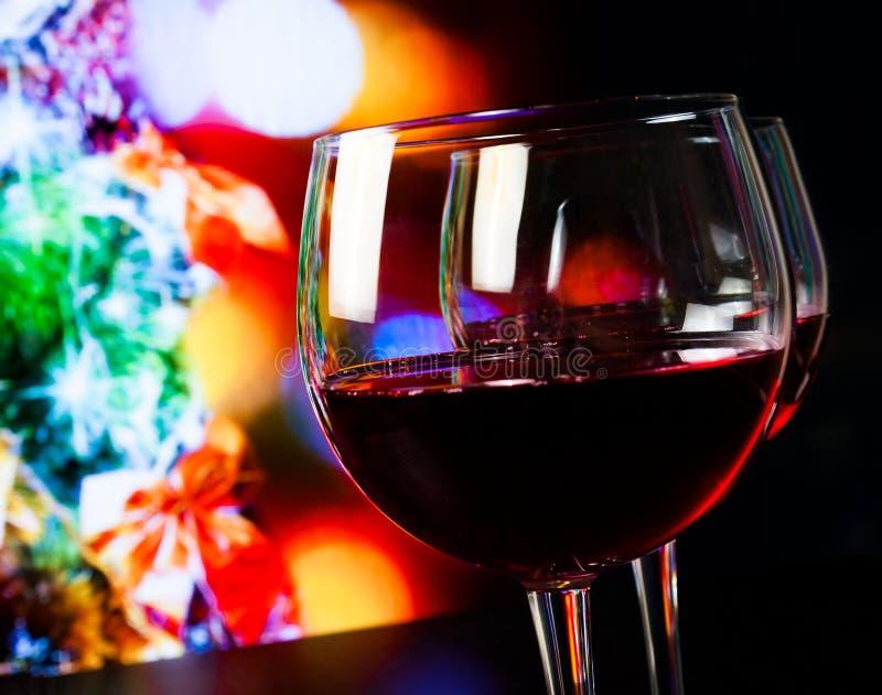 Δύο γυαλιά κόκκινου κρασιού στον ξύλινο πίνακα στο ελαφρύ κλίμα χριστουγεννιάτικων δέντρων στοκ φωτογραφίες