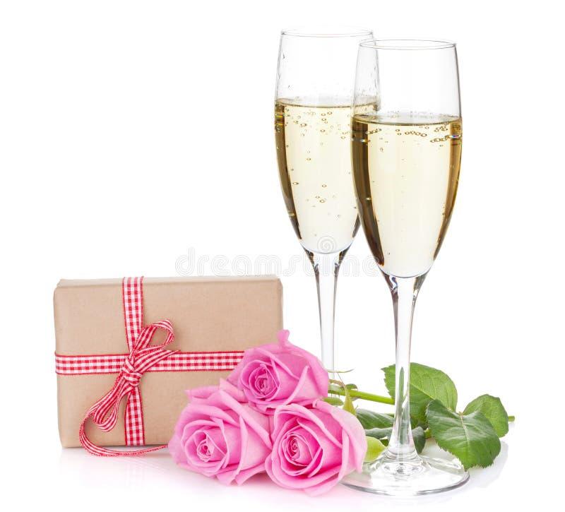 Δύο γυαλιά σαμπάνιας, κιβώτιο δώρων και ρόδινος αυξήθηκαν λουλούδια στοκ εικόνες
