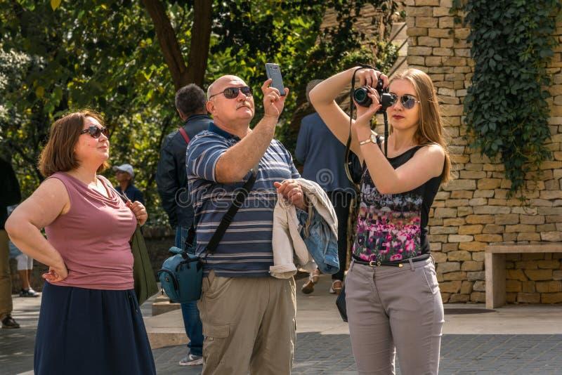 Δύο γυναίκα και ένας άνδρας που παίρνουν τις εικόνες με ένα τηλέφωνο και μια κάμερα της Mobil στη Βουδαπέστη Ουγγαρία στοκ φωτογραφίες