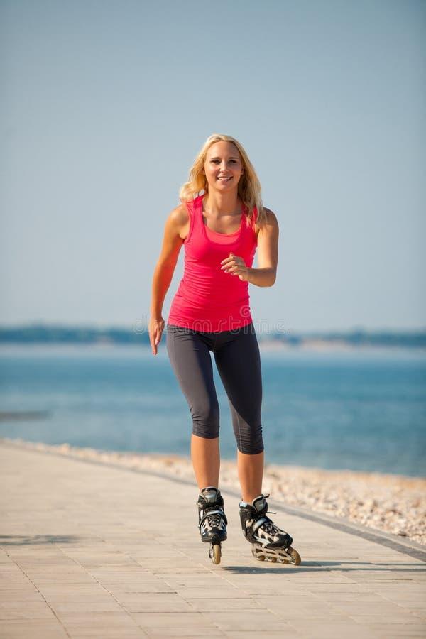 Δύο γυναίκες ασκούν στο τρέξιμο παραλιών και rollerblade το πατινάζ πλησίον στοκ εικόνες