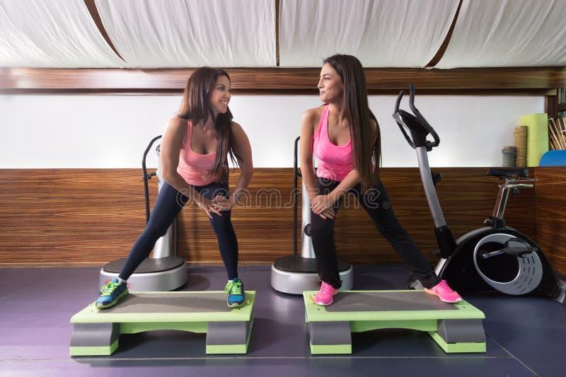 Δύο γυναίκες ασκούν την τεντώνοντας stepper γυμναστική στοκ εικόνα