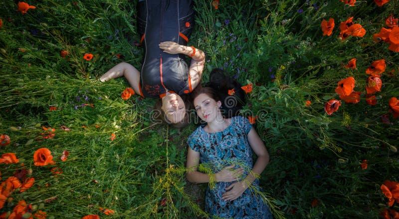 Δύο γυναίκες βάζουν στον τομέα λουλουδιών παπαρουνών στοκ εικόνες