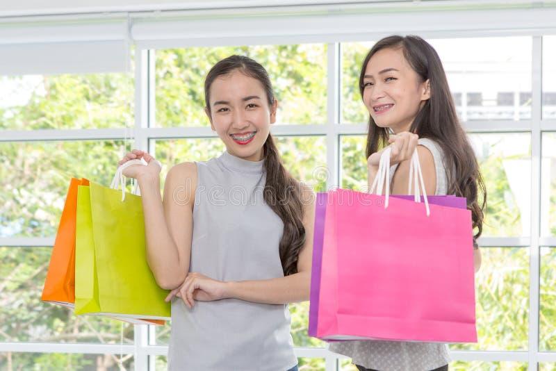 Δύο γυναίκες ευχαριστημένες από τις αγορές τοποθετούν σε σάκκο σε διαθεσιμότητα Γυναικείο smilin αγορών στοκ εικόνα