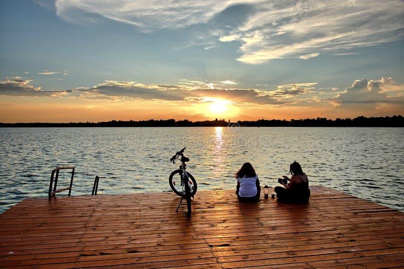 Δύο γυναίκες με το ποδήλατο στη λίμνη Palic στο ηλιοβασίλεμα, Σερβία στοκ εικόνες