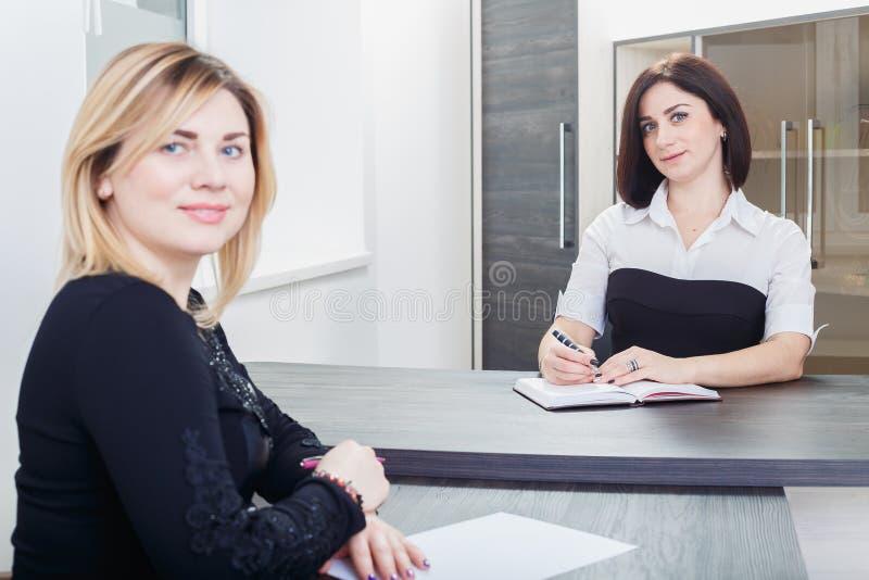 Δύο γυναίκες που κάθονται σε έναν πίνακα στο γραφείο Ξανθός και brunette στη συνέντευξη εργασίας, ή συνεδρίαση στοκ εικόνα με δικαίωμα ελεύθερης χρήσης