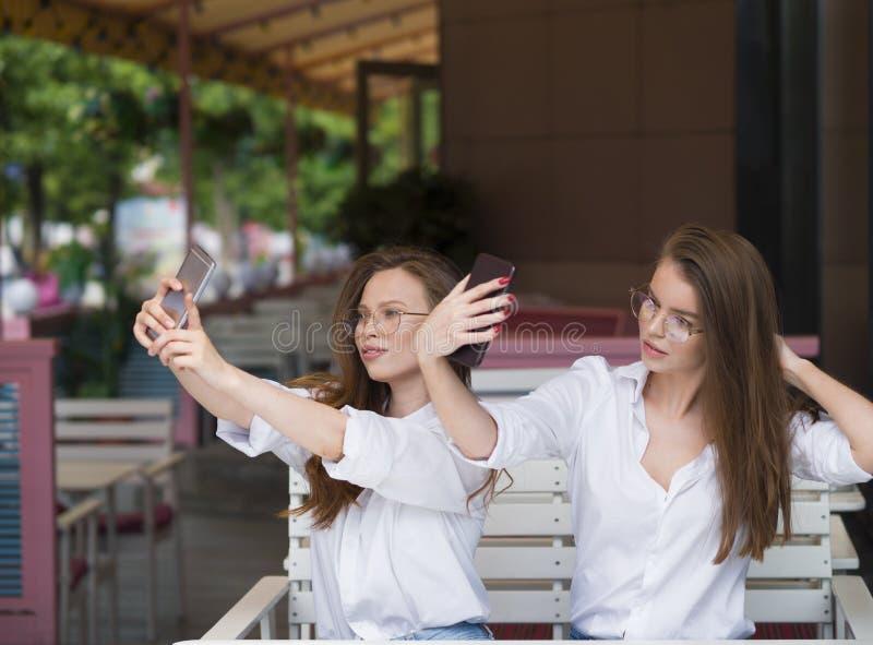 Δύο γυναίκες που κάνουν ένα selfie καθμένος σε έναν θερινό καφέ Συνεδρίαση και φιλία Κοινωνική έννοια δικτύων στοκ φωτογραφίες