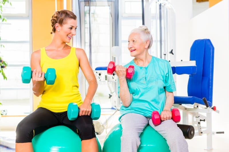 Δύο γυναίκες που κάνουν τον αθλητισμό δύναμης στη γυμναστική ικανότητας στοκ φωτογραφία με δικαίωμα ελεύθερης χρήσης