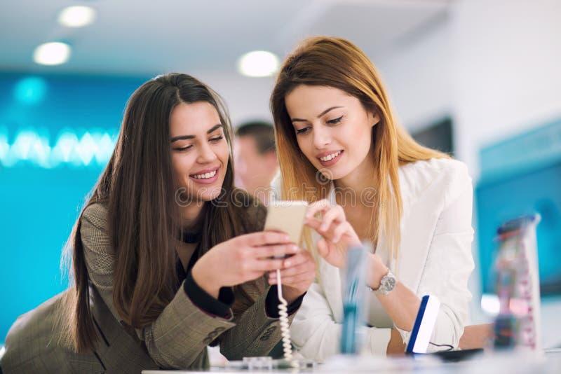 Δύο γυναίκες που κρατούν ένα κινητό τηλέφωνο στο κατάστημα στοκ φωτογραφία με δικαίωμα ελεύθερης χρήσης