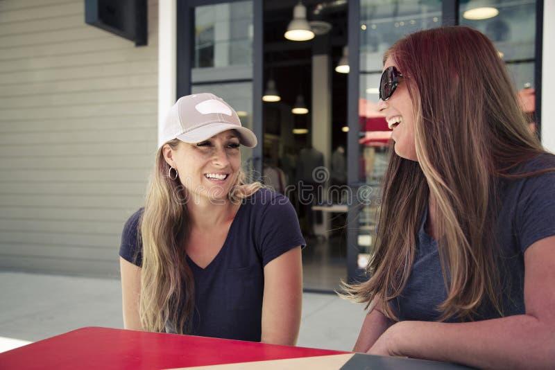 Δύο γυναίκες που κρεμούν έξω και που μιλούν σε έναν υπαίθριο καφέ σε έν στοκ εικόνα με δικαίωμα ελεύθερης χρήσης