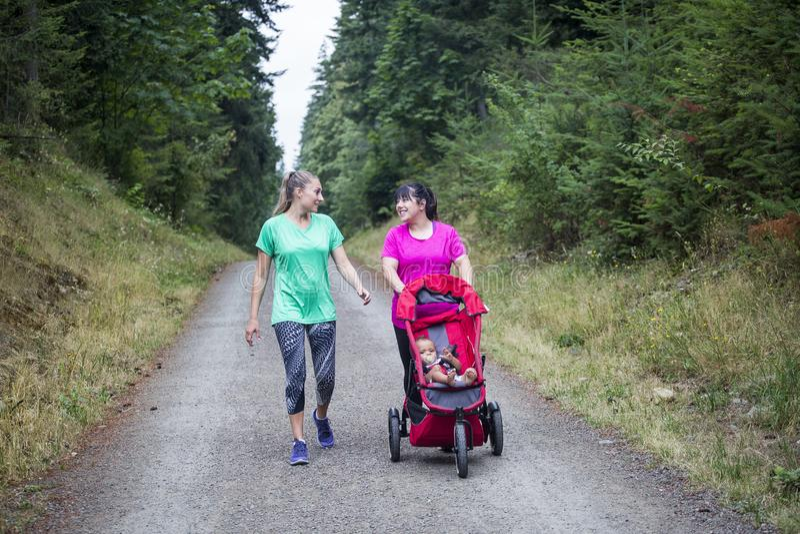 Δύο γυναίκες που περπατούν και που μιλούν μαζί σε ένα ίχνος με έναν περιπατητή μωρών στοκ φωτογραφία με δικαίωμα ελεύθερης χρήσης