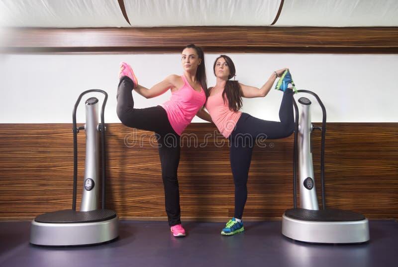 Δύο γυναίκες που στέκονται σε ένα τέντωμα ποδιών εκμετάλλευσης ποδιών στοκ φωτογραφίες