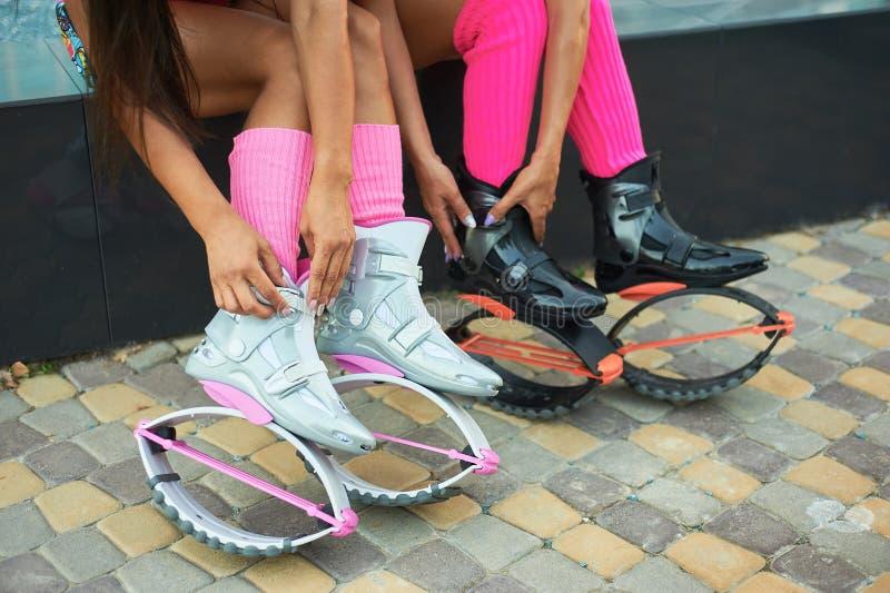 Δύο γυναίκες που τίθενται στις μπότες αλμάτων kangoo πριν από το workout στοκ εικόνα με δικαίωμα ελεύθερης χρήσης