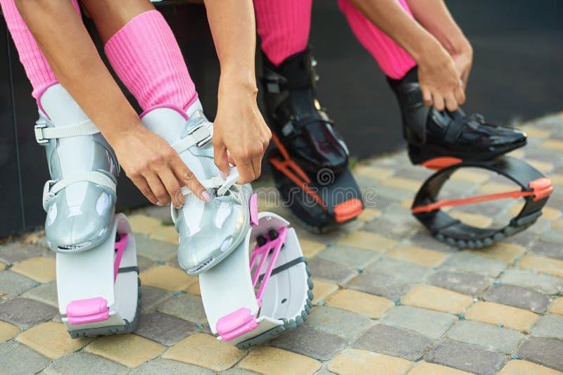 Δύο γυναίκες που τίθενται στις μπότες αλμάτων kangoo πριν από το workout στοκ εικόνες