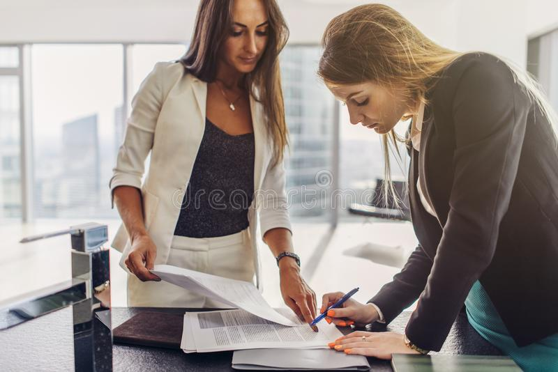 Δύο γυναίκες που υπογράφουν μια σύμβαση που στέκεται στο σύγχρονο διαμέρισμα στοκ εικόνες με δικαίωμα ελεύθερης χρήσης