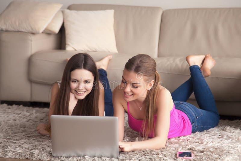 Δύο γυναίκες που χρησιμοποιούν το lap-top κατά στον τάπητα στοκ εικόνες