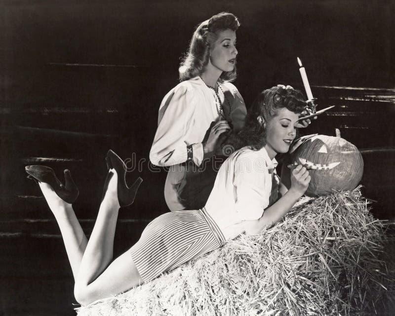 Δύο γυναίκες σε έναν χαράζοντας γρύλο σιταποθηκών o'lantern στοκ εικόνες με δικαίωμα ελεύθερης χρήσης