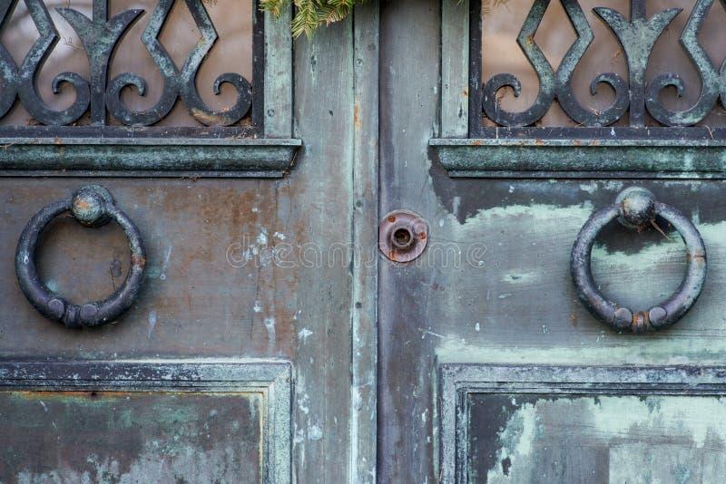 Δύο δαχτυλίδια ρόπτρων στην εκλεκτής ποιότητας αγροτική πόρτα Παλαιά εξογκώματα πορτών στοκ φωτογραφία