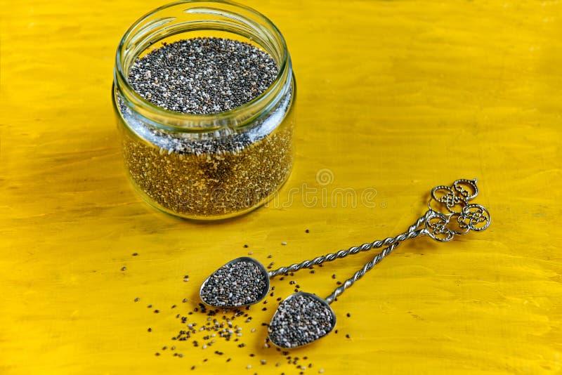 Δύο εκλεκτής ποιότητας βάζο κουταλιών και glas με τους φρέσκους σπόρους chia στο κίτρινο ξύλινο υπόβαθρο με το ελεύθερο διάστημα  στοκ εικόνα με δικαίωμα ελεύθερης χρήσης