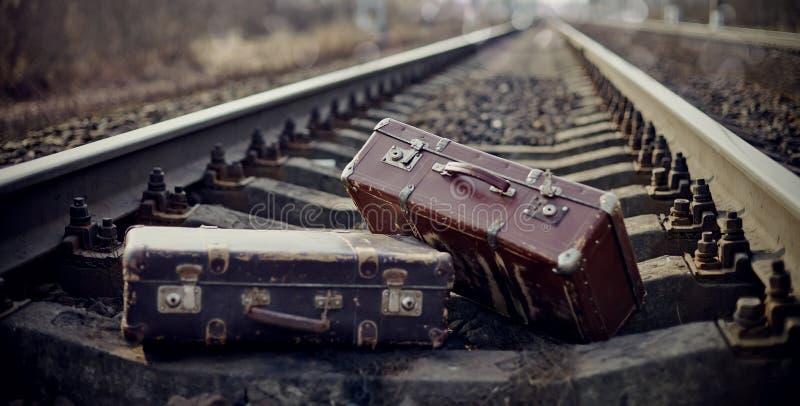Δύο εκλεκτής ποιότητας βαλίτσες που ρίχνονται στις ράγες σιδηροδρόμων στοκ εικόνες με δικαίωμα ελεύθερης χρήσης