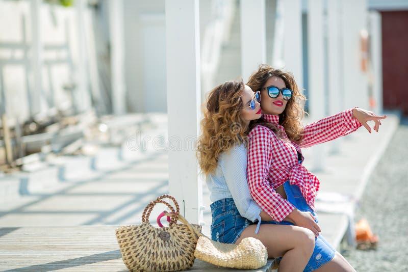 Δύο ελκυστικά κορίτσια, εύθυμοι καλύτεροι φίλοι που έχουν τη διασκέδαση στο κόμμα παραλιών Φθορά της θερινών εξάρτησης, των σορτς στοκ εικόνες με δικαίωμα ελεύθερης χρήσης