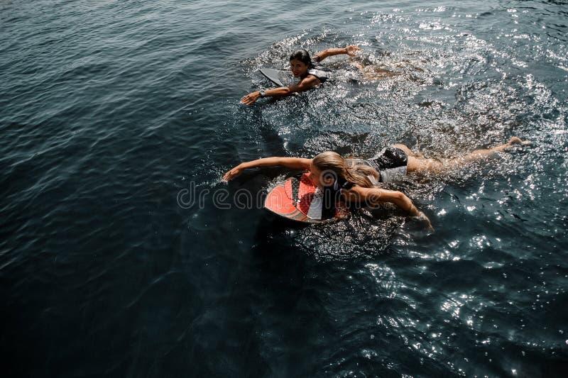 Δύο ελκυστικά κορίτσια που κολυμπούν στο wakeboard στοκ εικόνες