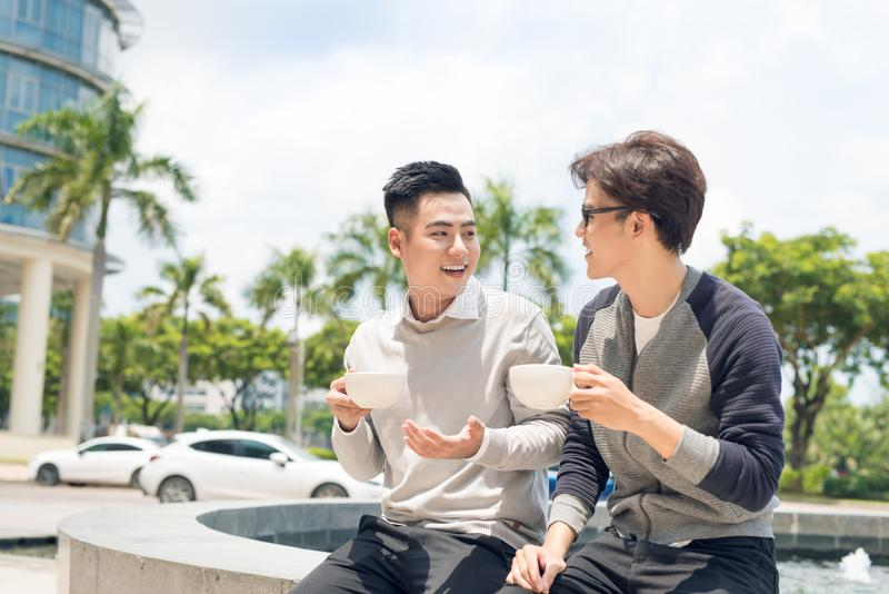 Δύο ενήλικοι αρσενικοί φίλοι κάθονται την ομιλία πέρα από τον καφέ έξω από τον καφέ στοκ φωτογραφία με δικαίωμα ελεύθερης χρήσης