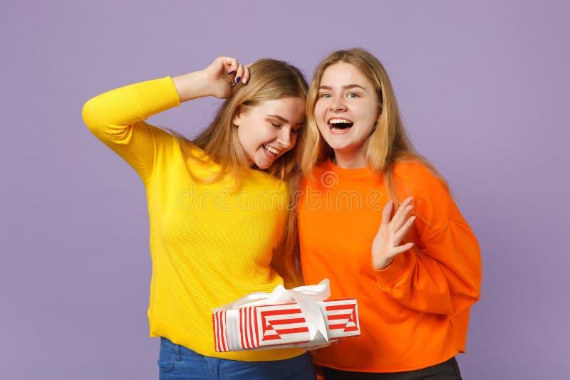 Δύο εξέπληξαν τα ξανθά κορίτσια αδελφών διδύμων στο ζωηρό κόκκινο ριγωτό παρόν κιβώτιο λαβής ενδυμάτων με την κορδέλλα δώρων που  στοκ εικόνα με δικαίωμα ελεύθερης χρήσης