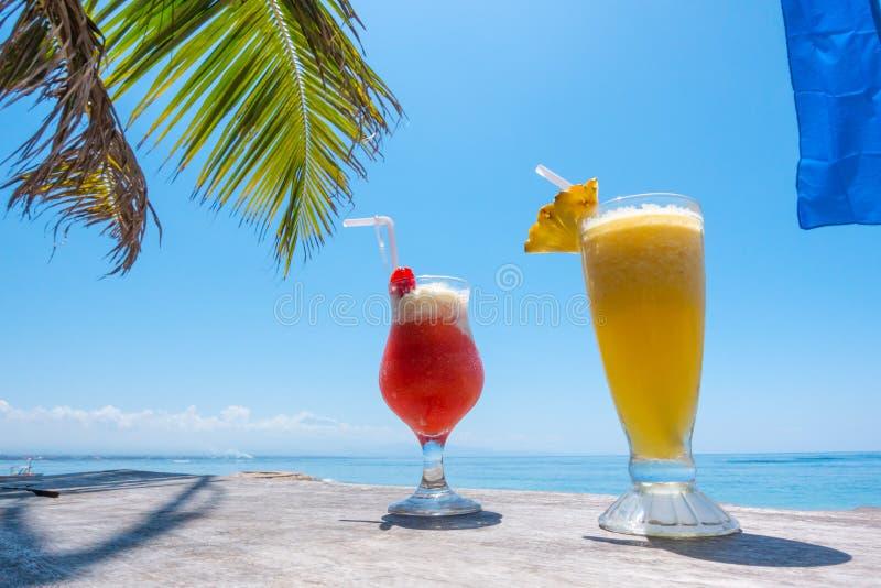 Δύο εξωτικά κοκτέιλ στον πίνακα στην τροπική παραλία στοκ εικόνα με δικαίωμα ελεύθερης χρήσης