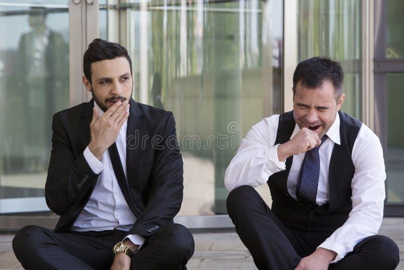 Δύο επιχειρηματίες που κάθονται έξω και χασμουριούνται στοκ εικόνες