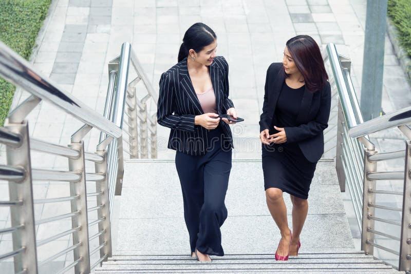 Δύο επιχειρηματίες που περπατούν επάνω στο σκαλοπάτι και που μιλούν από κοινού Έννοια επιχειρήσεων και εργασίας Έννοια εργασίας κ στοκ εικόνες