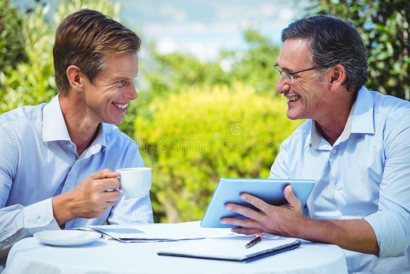 Δύο επιχειρηματίες που συναντιούνται σε ένα εστιατόριο που χρησιμοποιεί την ταμπλέτα στοκ εικόνα