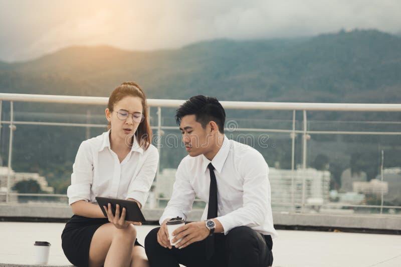 Δύο επιχειρηματίες που χρησιμοποιούν την ψηφιακή ταμπλέτα στο εξωτερικό επιχειρησιακό γραφείο από κοινού στοκ εικόνες