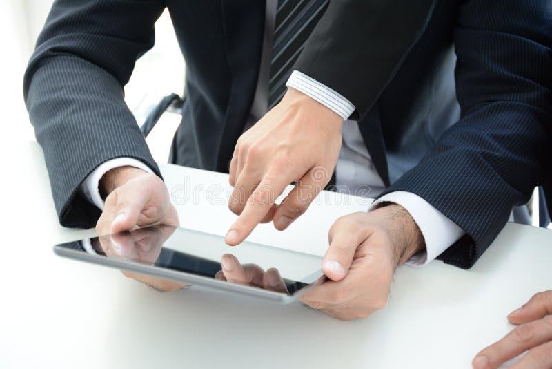 Δύο επιχειρηματίες που χρησιμοποιούν τον υπολογιστή ταμπλετών με ένα χέρι σχετικά με την οθόνη στοκ εικόνες με δικαίωμα ελεύθερης χρήσης