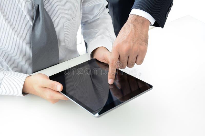 Δύο επιχειρηματίες που χρησιμοποιούν τον υπολογιστή ταμπλετών με ένα χέρι σχετικά με την οθόνη στοκ φωτογραφία με δικαίωμα ελεύθερης χρήσης
