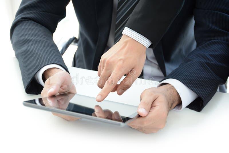 Δύο επιχειρηματίες που χρησιμοποιούν τον υπολογιστή ταμπλετών με ένα χέρι σχετικά με την οθόνη στοκ εικόνα με δικαίωμα ελεύθερης χρήσης