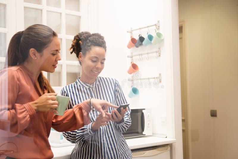 Δύο επιχειρησιακές γυναίκες που δείχνουν σε ένα τηλέφωνο σε ένα kitche στοκ φωτογραφίες με δικαίωμα ελεύθερης χρήσης