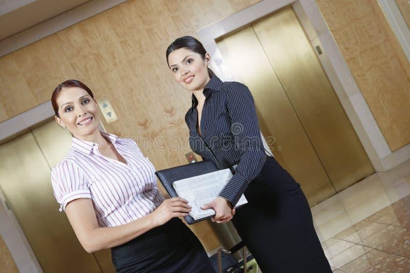 Δύο επιχειρησιακές γυναίκες στο διάδρομο γραφείων στοκ φωτογραφία