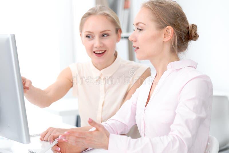 Δύο επιχειρησιακοί κυρίες ή συνάδελφοι που συζητούν κάτι στο υπόβαθρο γραφείων στοκ φωτογραφία