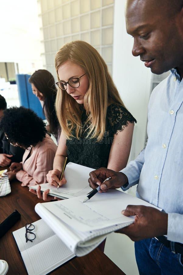 Δύο επιχειρησιακοί συνάδελφοι που συγκρίνουν τις σημειώσεις εργασίας μαζί σε ένα γραφείο στοκ εικόνες