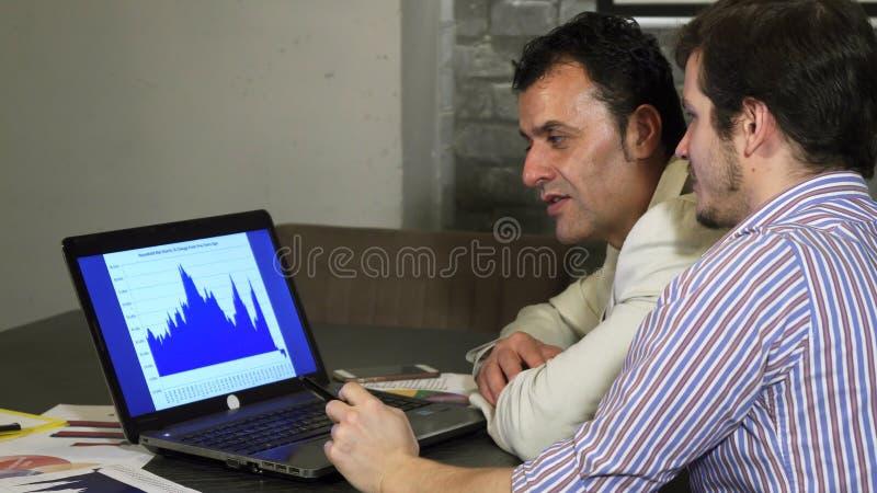 Δύο επιχειρησιακοί συνάδελφοι που συζητούν το διάγραμμα στο lap-top στοκ φωτογραφία