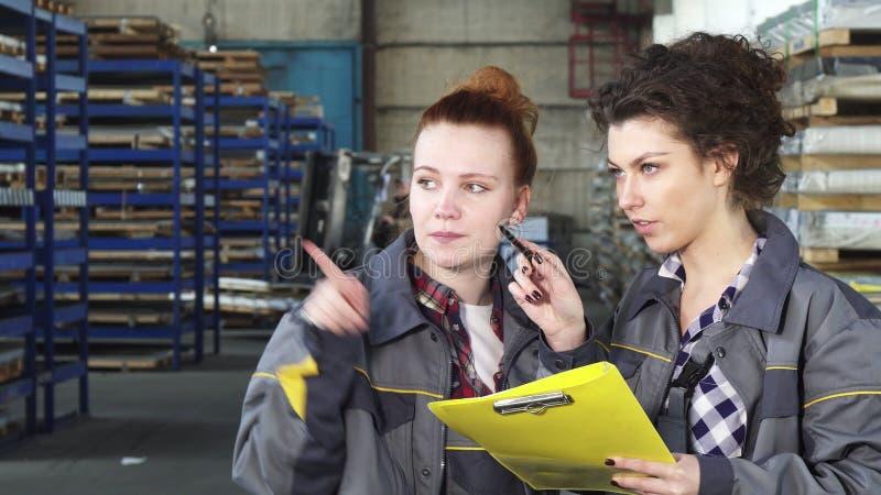 Δύο εργαζόμενοι αποθηκών εμπορευμάτων θηλυκών που εξετάζουν τα έγγραφα από κοινού στοκ εικόνα
