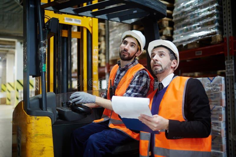 Δύο εργαζόμενοι αποθηκών εμπορευμάτων που οδηγούν Forklift το φορτηγό στοκ εικόνα