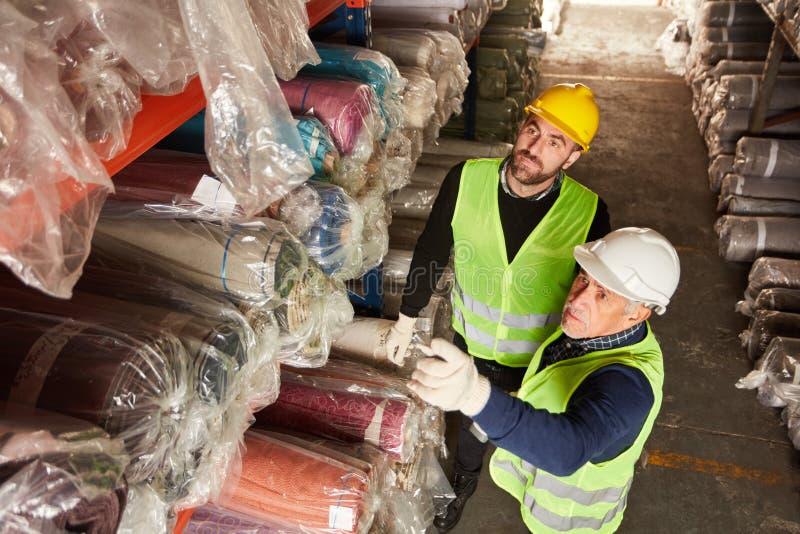 Δύο εργαζόμενοι αποθηκών εμπορευμάτων στην αποθήκη εμπορευμάτων ταπήτων στοκ φωτογραφίες με δικαίωμα ελεύθερης χρήσης