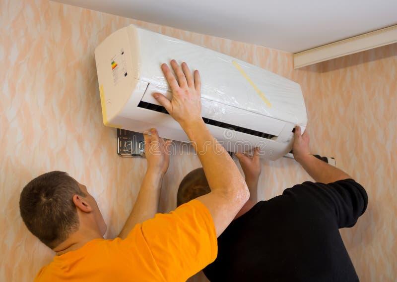 Δύο εργαζόμενοι εγκαθιστούν το κλιματιστικό μηχάνημα στο διαμέρισμα στοκ φωτογραφία με δικαίωμα ελεύθερης χρήσης