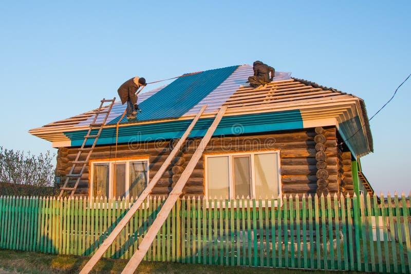 Δύο εργαζόμενοι καλύπτουν τη στέγη ενός αγροτικού σπιτιού με τα κεραμίδια μετάλλων στοκ εικόνα με δικαίωμα ελεύθερης χρήσης