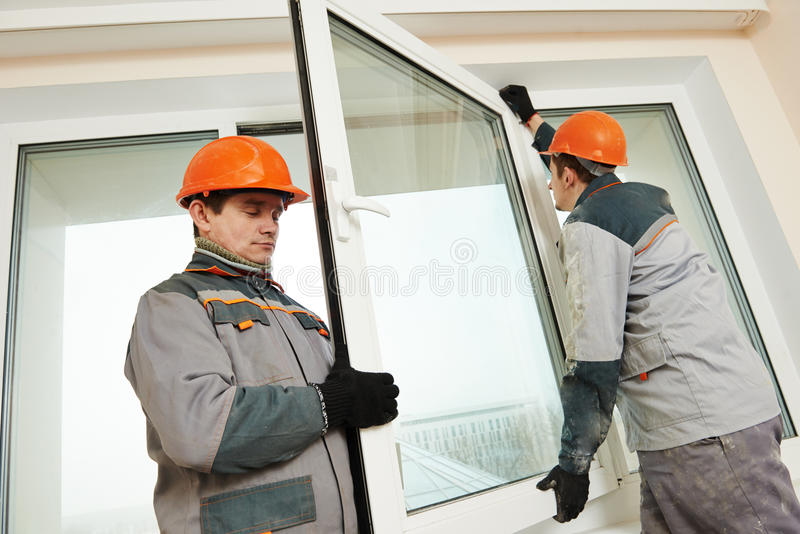 Δύο εργαζόμενοι που εγκαθιστούν το παράθυρο στοκ φωτογραφία